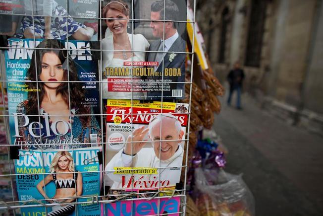 Banca de jornais com revistas de celebridades estampando o casal presidencial e o papa (Foto Reuters)