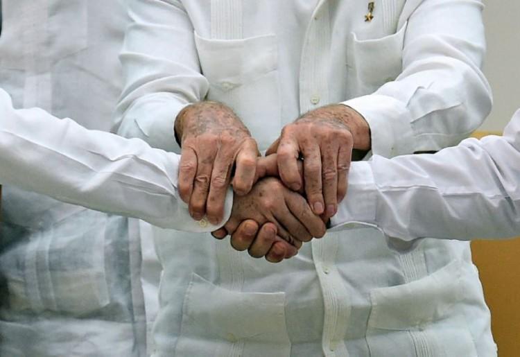 As mãos de Timochenko, Santos e Raúl Castro, em encontro das equipes negociadoras em Cuba (Foto Reuters)